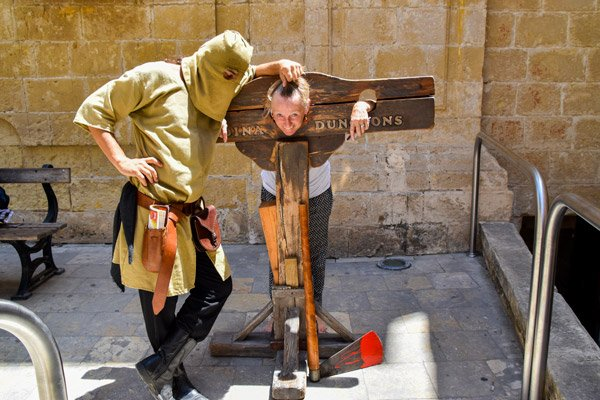 beul en toeriste spelend op het kapblok kerkers mdina malta