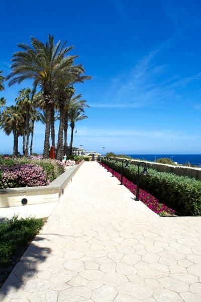 promenade dichtbij zwembaden met zicht op zee hilton malta hotel